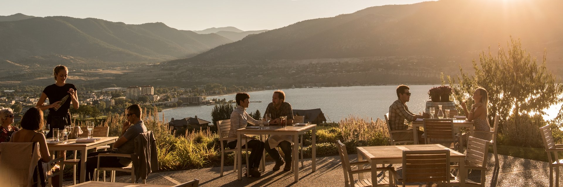 Patrons of The Vanilla Pod Restaurant at Poplar Grove winery enjoy dining on the patio with views of Okanagan Lake and Penticton, BC.