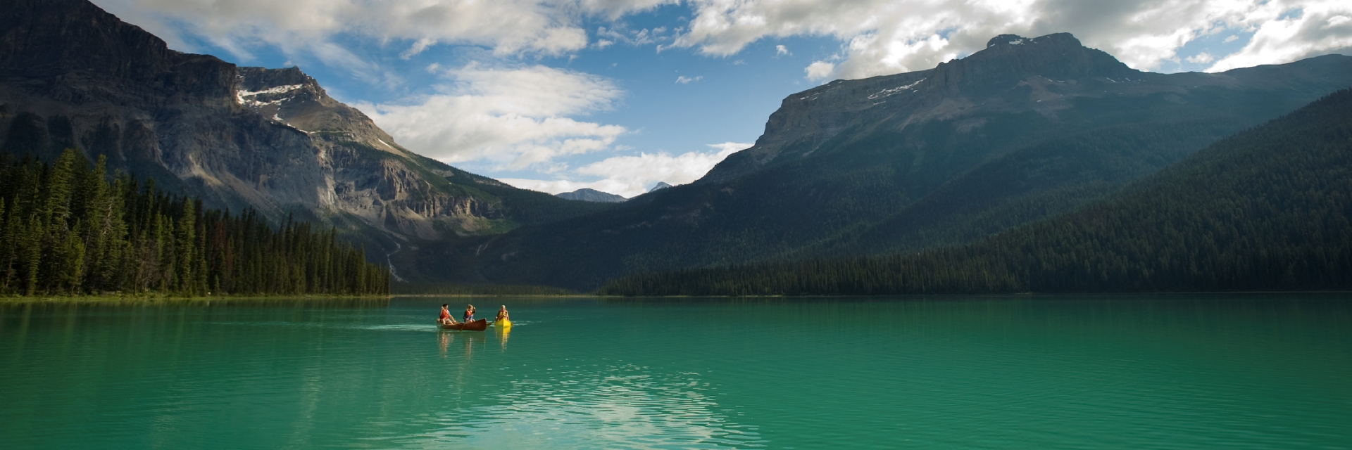 Two couples canoeing on Emerald Lake with views of the mountains in Yoho National Park near Field.