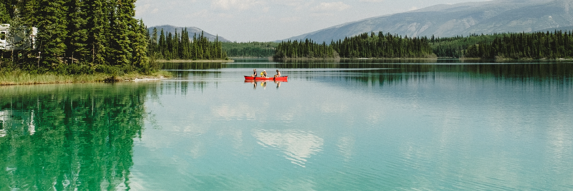 Two people in a red canoe on a bright turquoise lake.