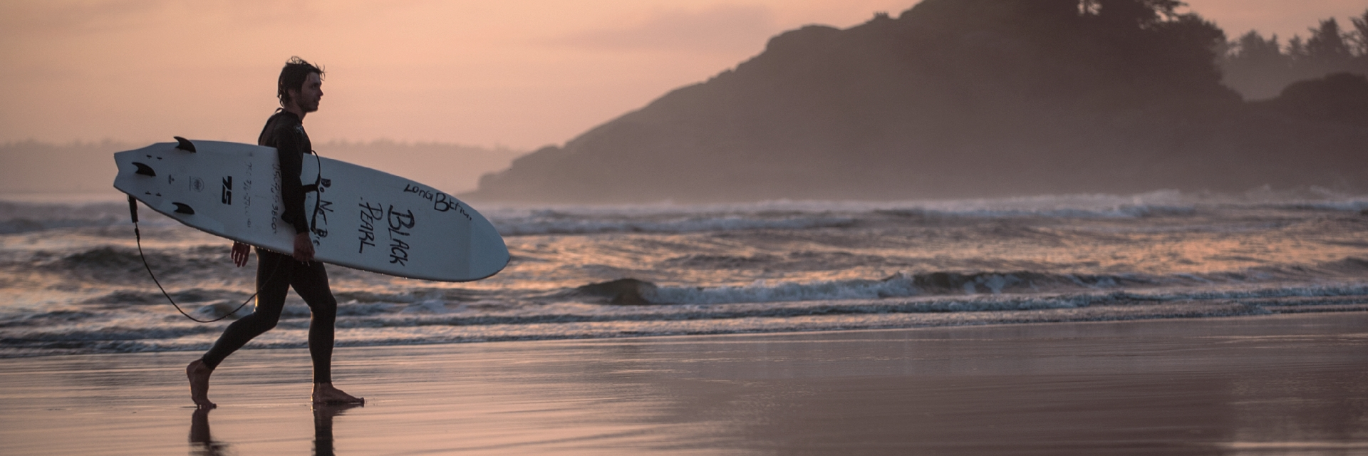 A surfer walks towards the water in Tofino.
