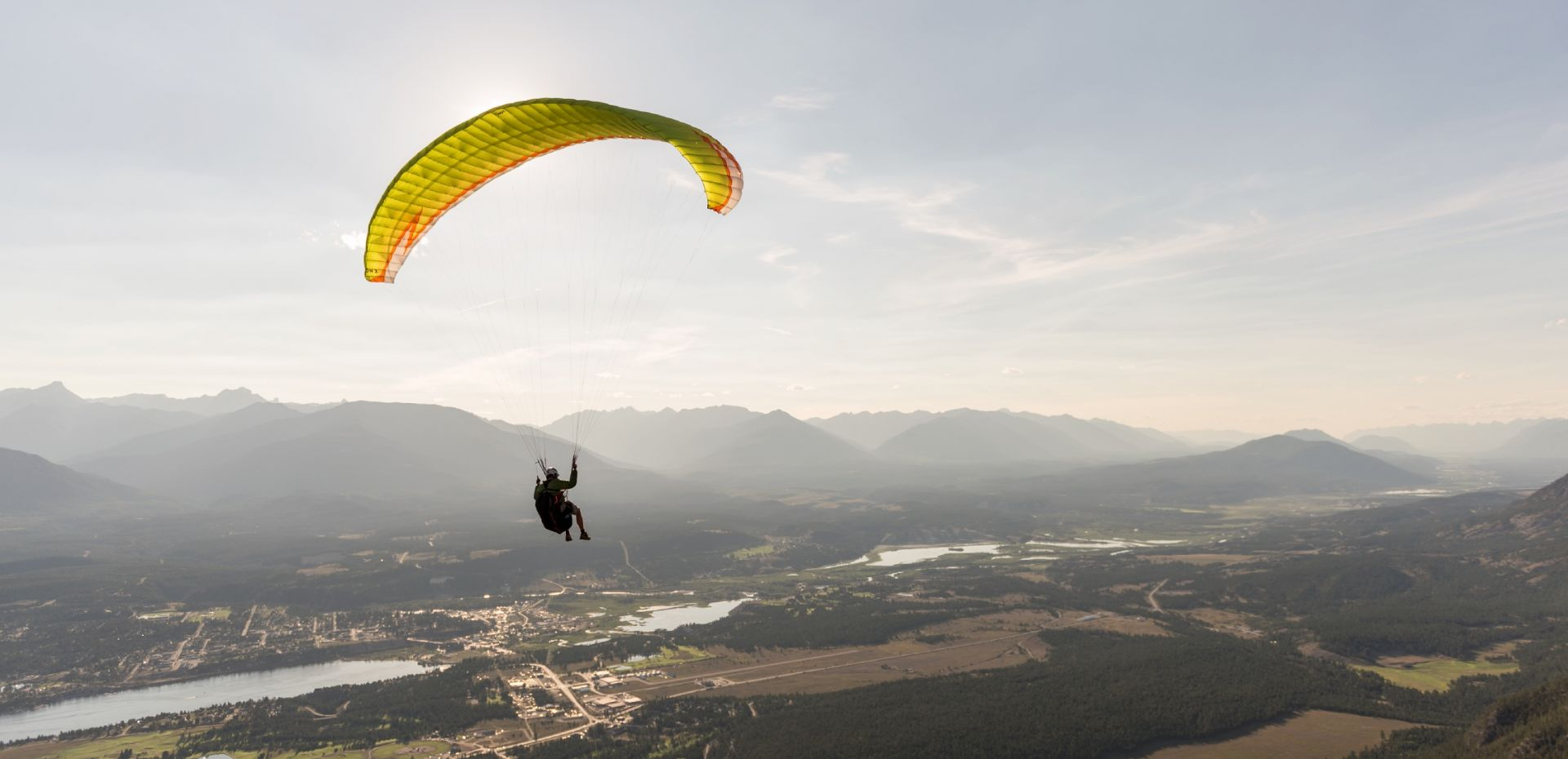 A paraglider over Mt. Swansea overlooking the Rocky Mountain Trench and Lake Windermere in Invermere, BC.
