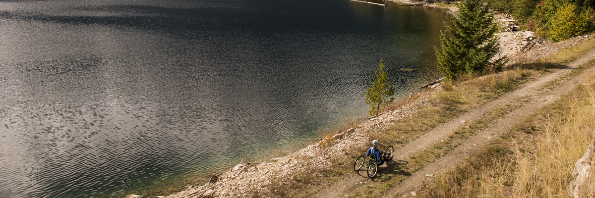 A man in a reclining wheelchair on a trail next to a lake in British Columbia